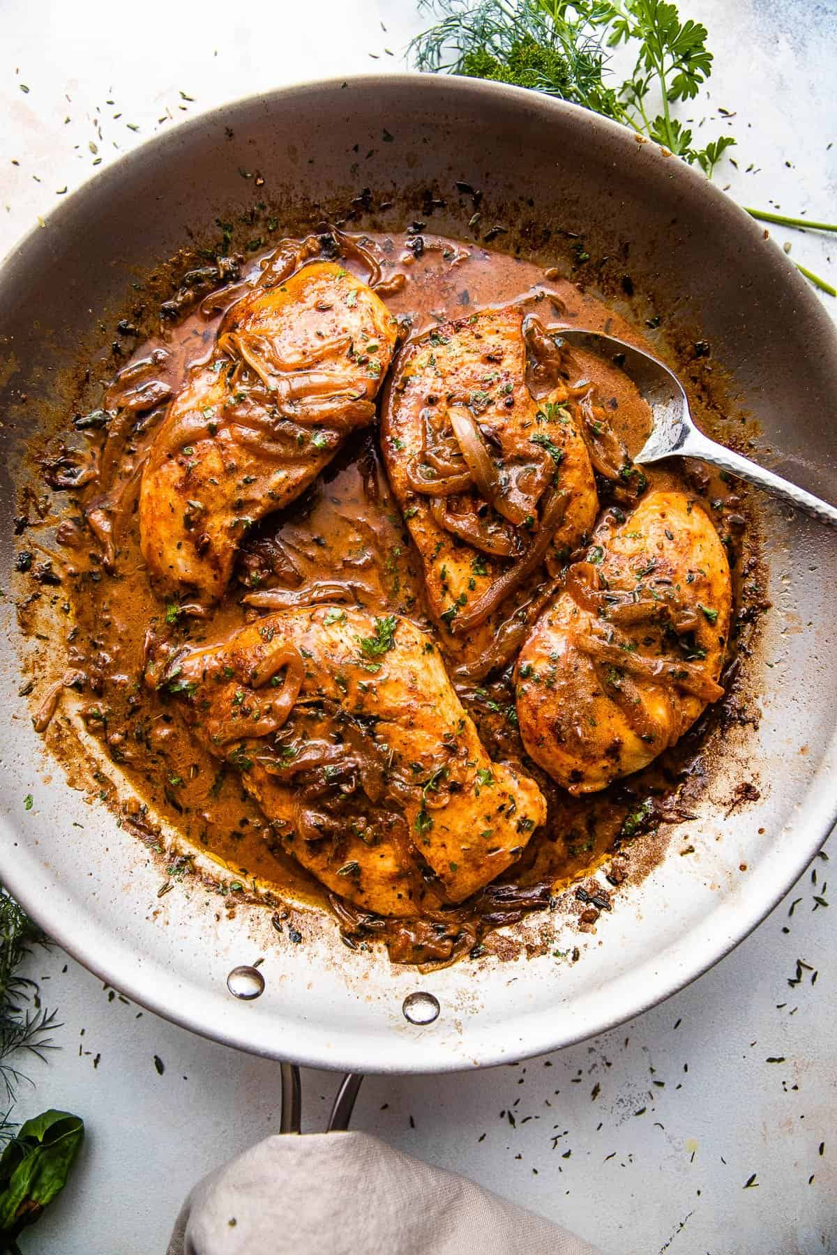 wide overhead shot of chicken breasts in a skillet with gravy