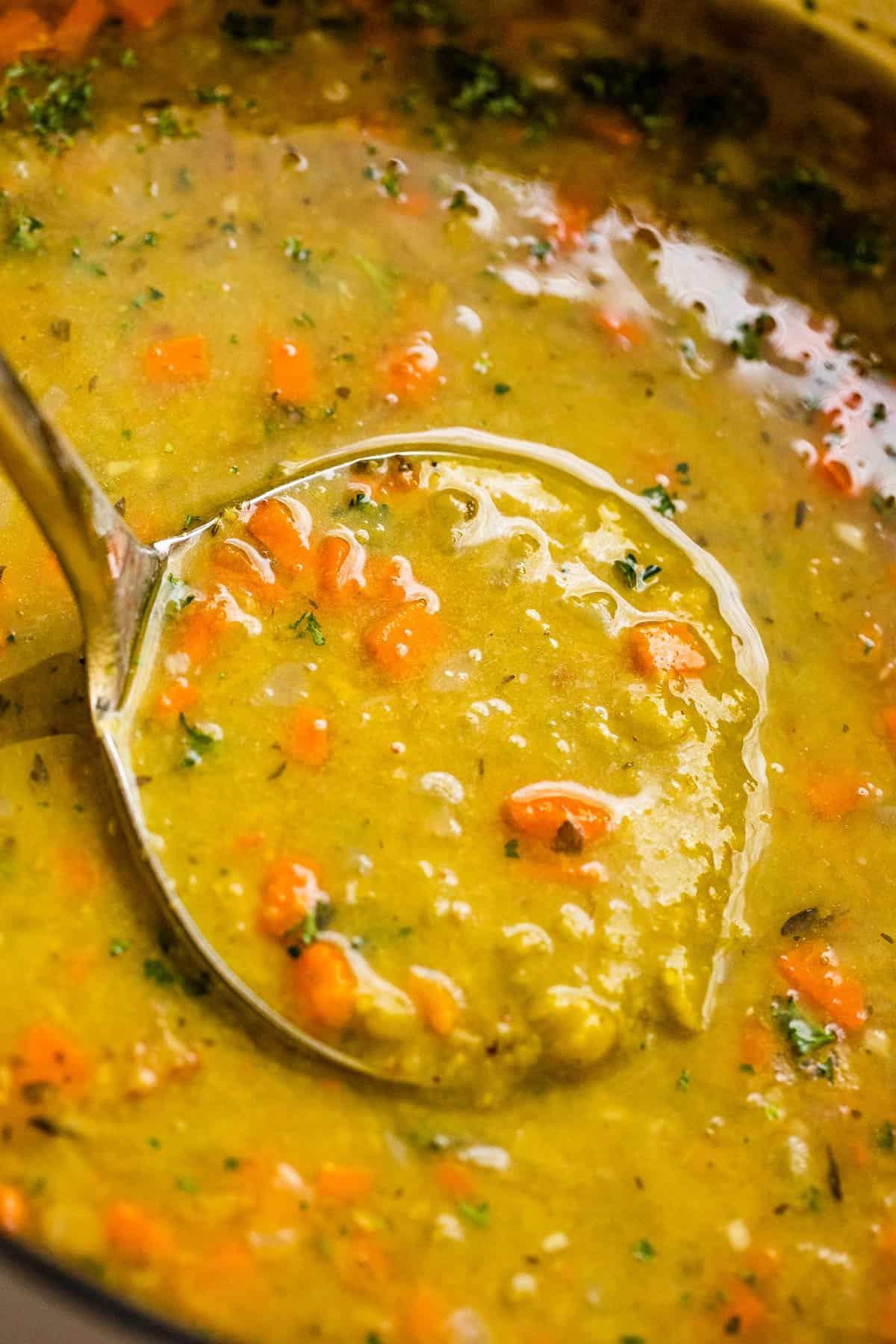 ladle inside split pea soup with ham