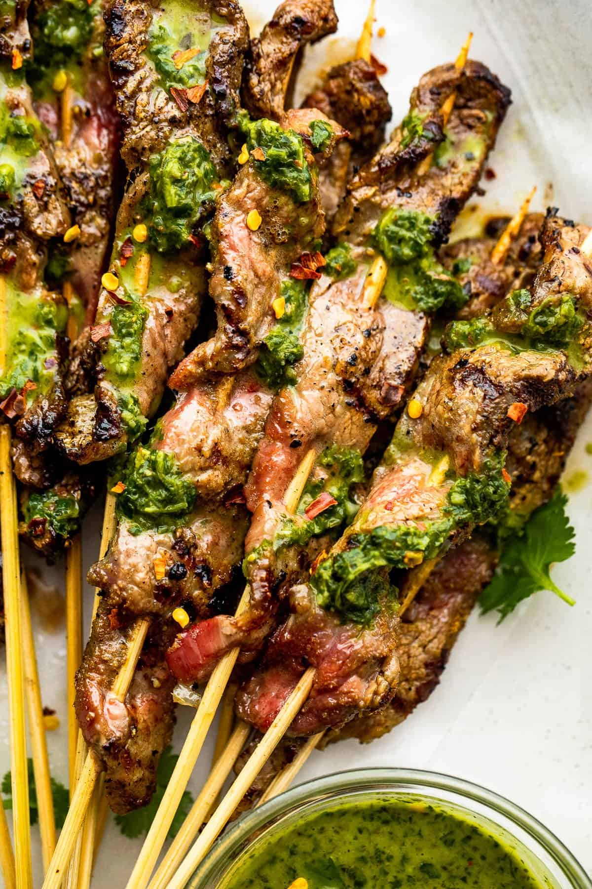 eight Grilled Steak Skewers served on a plate and topped with chimichurri sauce