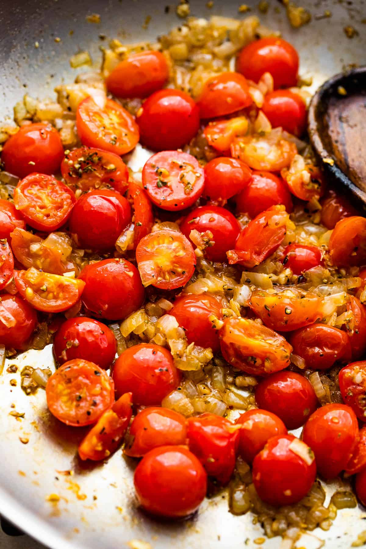 cooking halved cherry tomatoes in a skillet