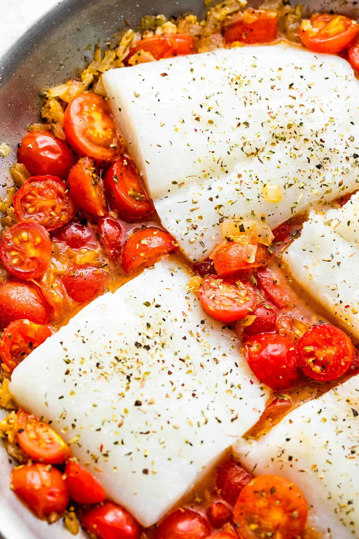raw cod fish on top of halved cherry tomatoes