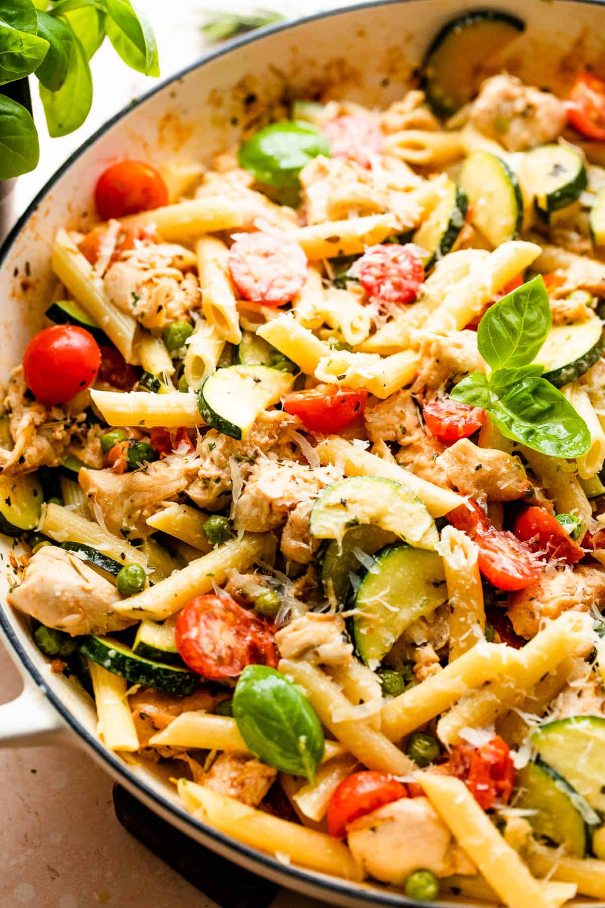penne pasta with zucchini, tomatoes, chicken, and peas in a skillet