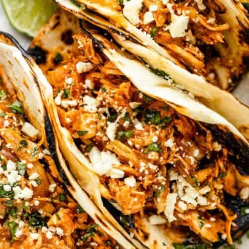 three chicken tinga tacos arranged on a plate and topped with cheese