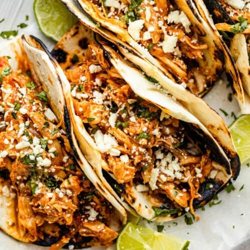 four chicken tinga tacos arranged on a plate and topped with cheese
