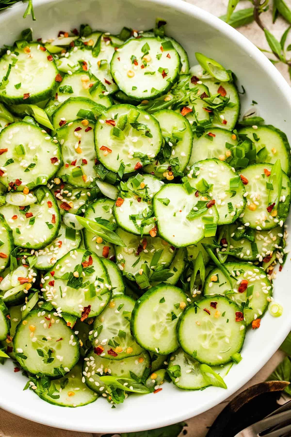 sesame cucumber salad served in a white salad bowl