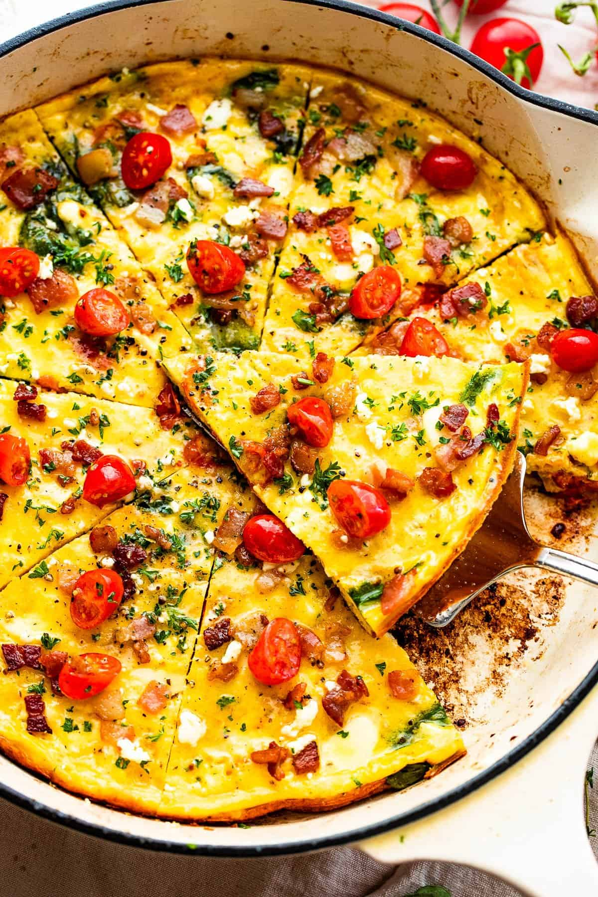 overhead shot of a sliced frittata in a white skillet topped with bacon and tomatoes