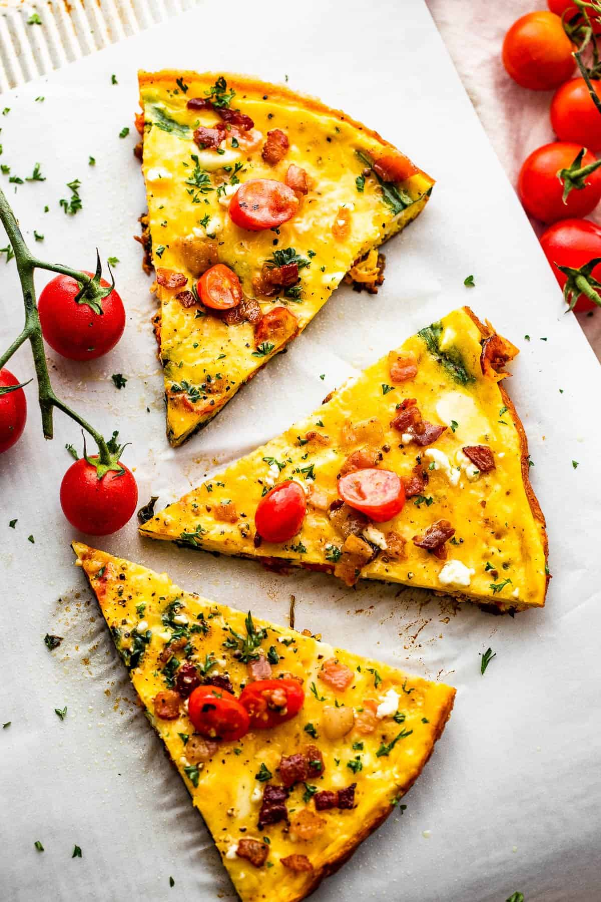 three slices of bacon tomato frittata arranged on a plate