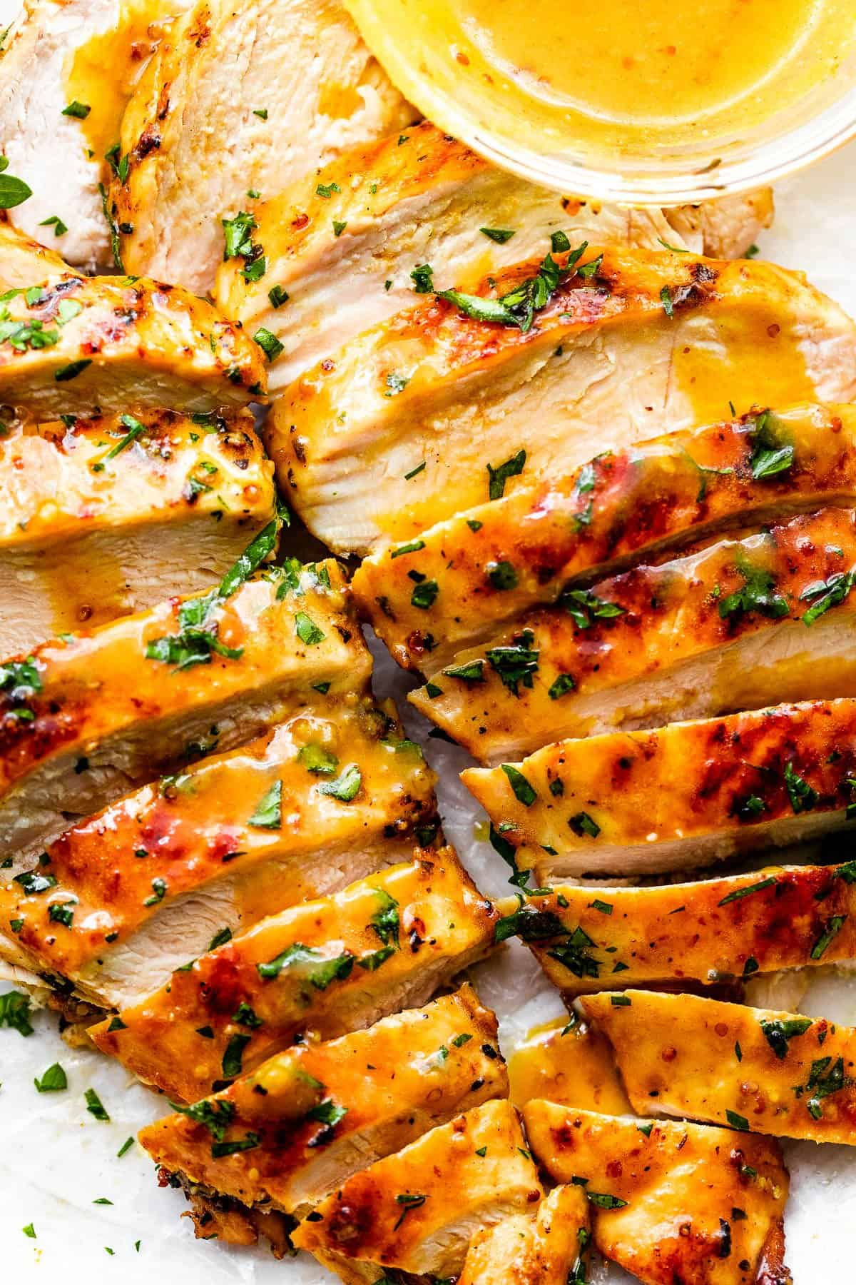 two grilled honey mustard chicken breasts cut into thin slices and served with honey mustard sauce on the side