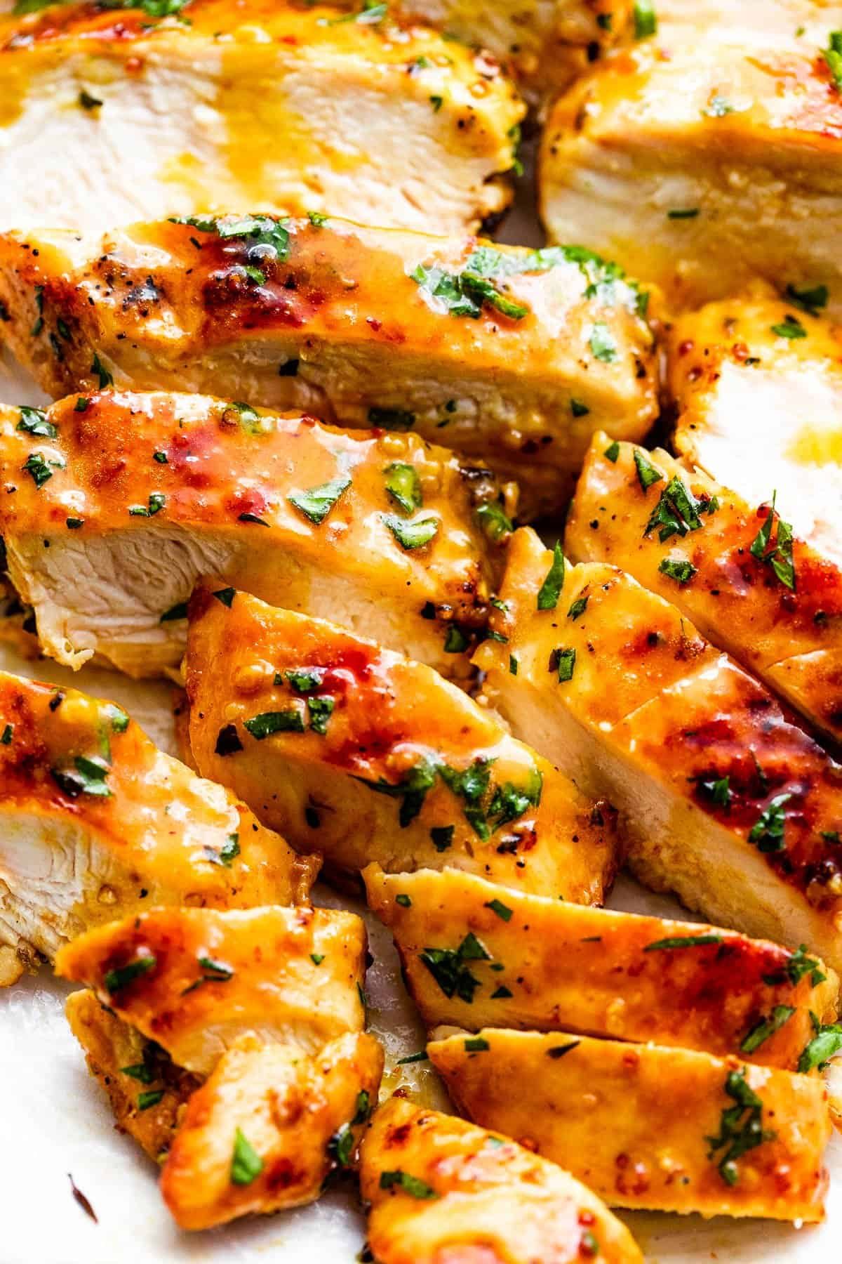 close up photo of grilled honey mustard chicken breasts cut into thin slices