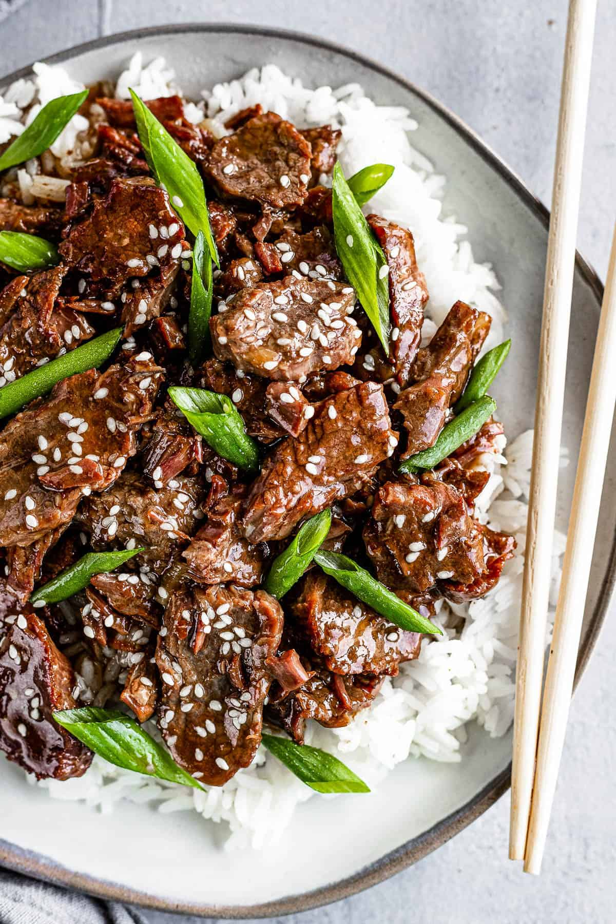 Instant Pot Mongolian Beef served over a bed of rice with chopsticks on the side