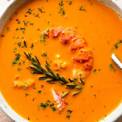 soup bowl with lobster bisque garnished with lobster meat and rosemary
