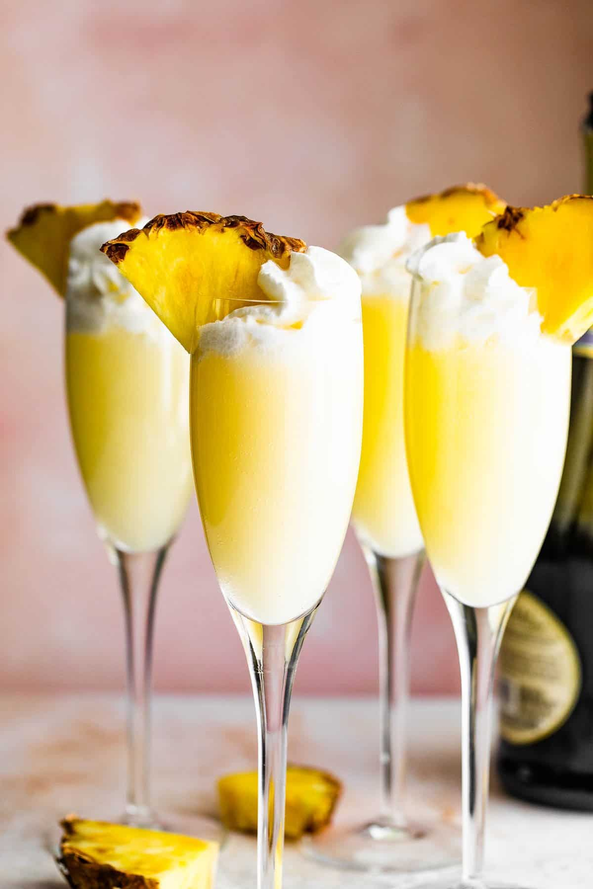 four champagne flutes filled with pineapple dole whip mimosas and topped with whipped cream and pineapple slices