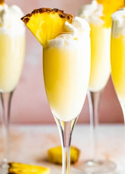 up close photo of champagne flutes with pineapple mimosas