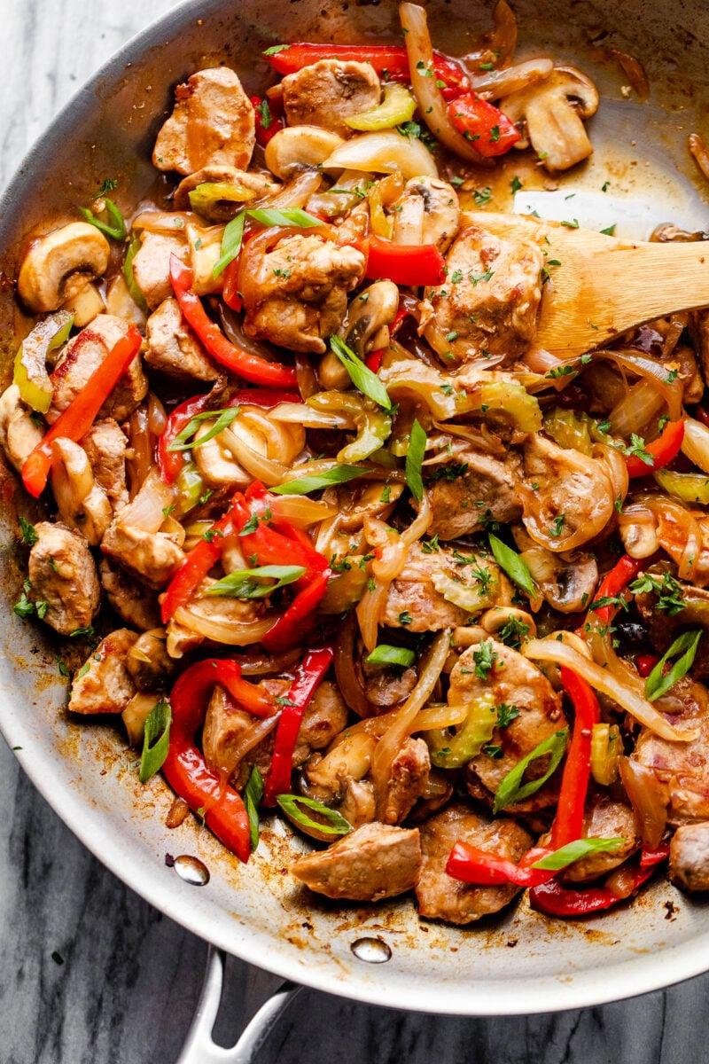 stirring pork chop suey in a skillet