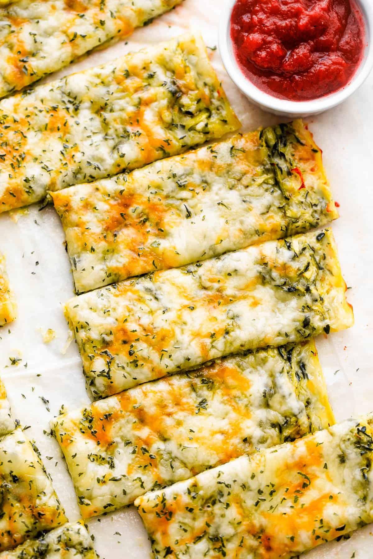 overhead shot of keto zucchini breadsticks with marinara sauce on the side