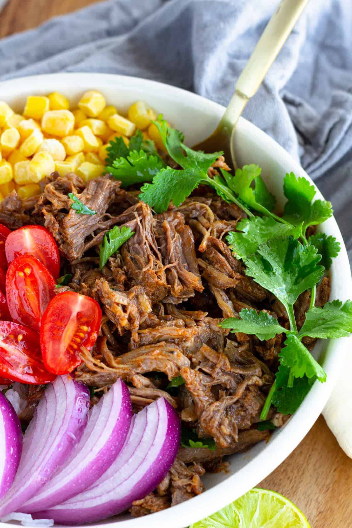 Instant Pot Beef Barbacoa served in a white large bowl with red onions, tomatoes, corn, and a garnish of cilantro