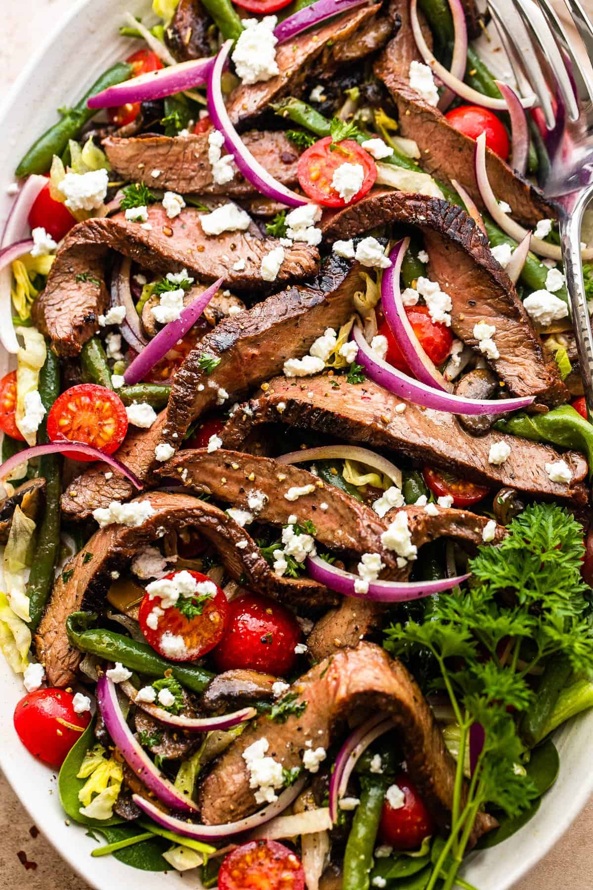 balsamic steak thinly sliced and served over lettuce with onions, grapes, and salad greens