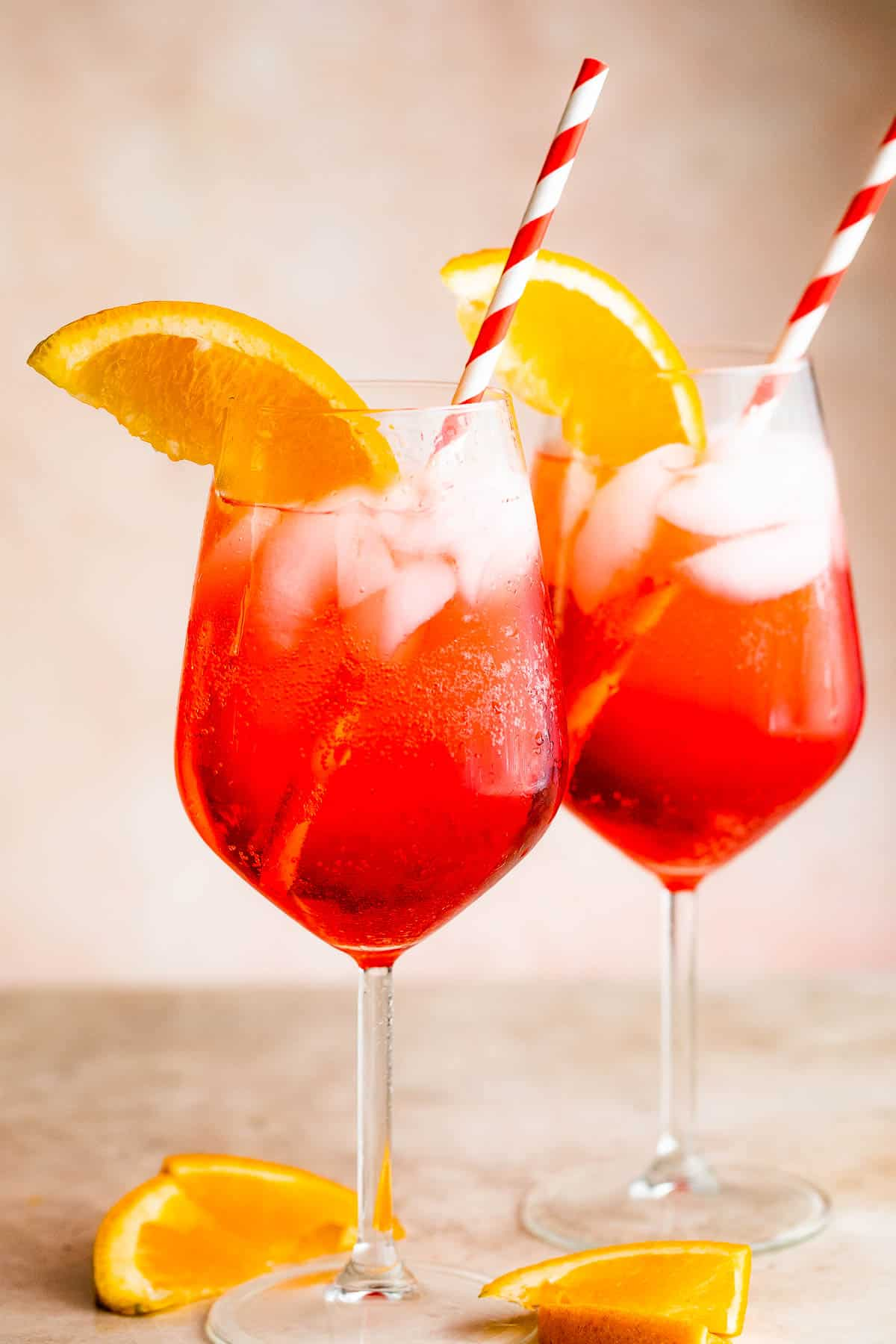 Two tall stemmed glasses with Campari Spritz served with a red and white straw
