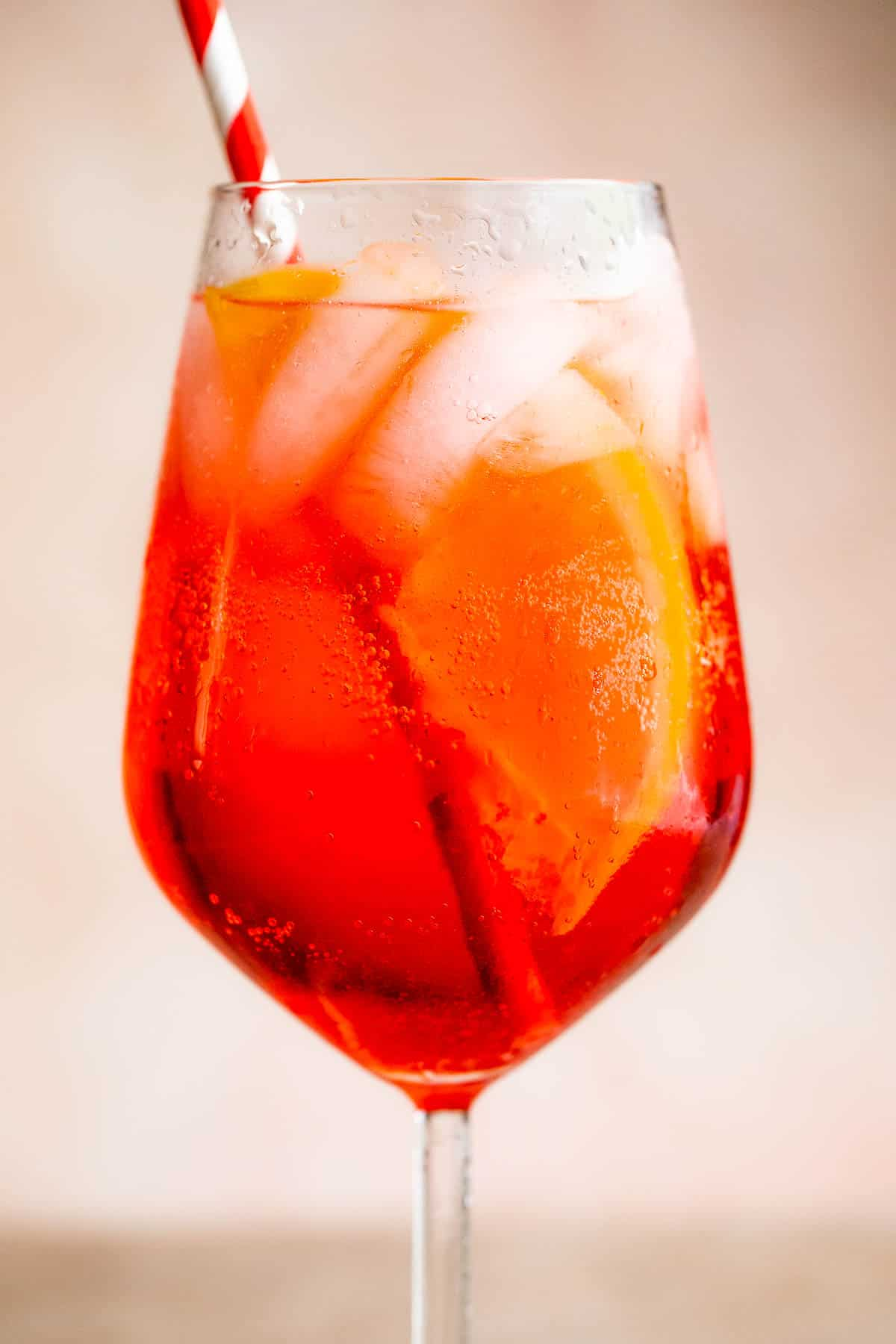 Campari Spritz in a tall stemmed glass served with a red and white straw
