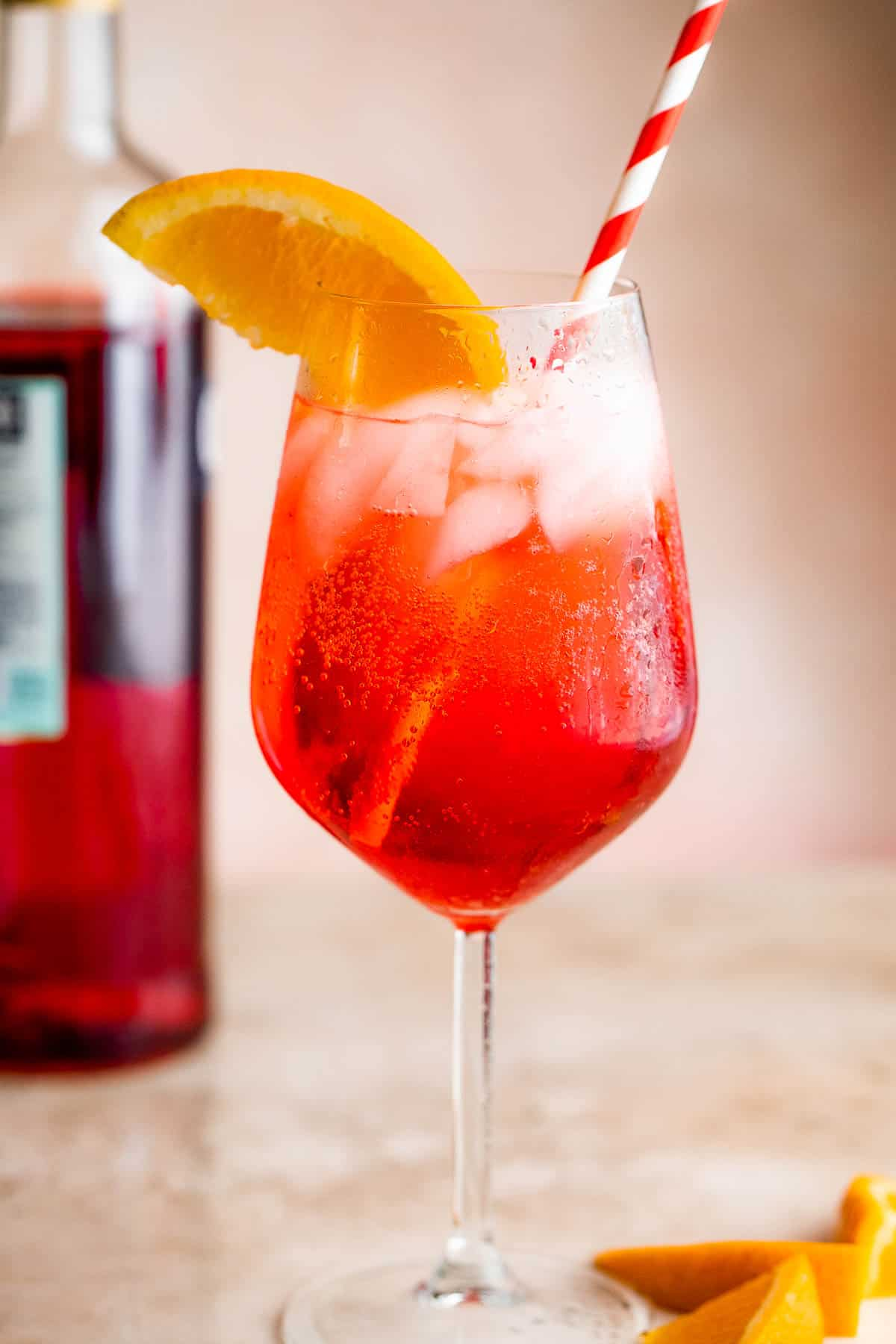 Campari Spritz in a tall stemmed glass served with a slice of orange on the rim and red and white straw