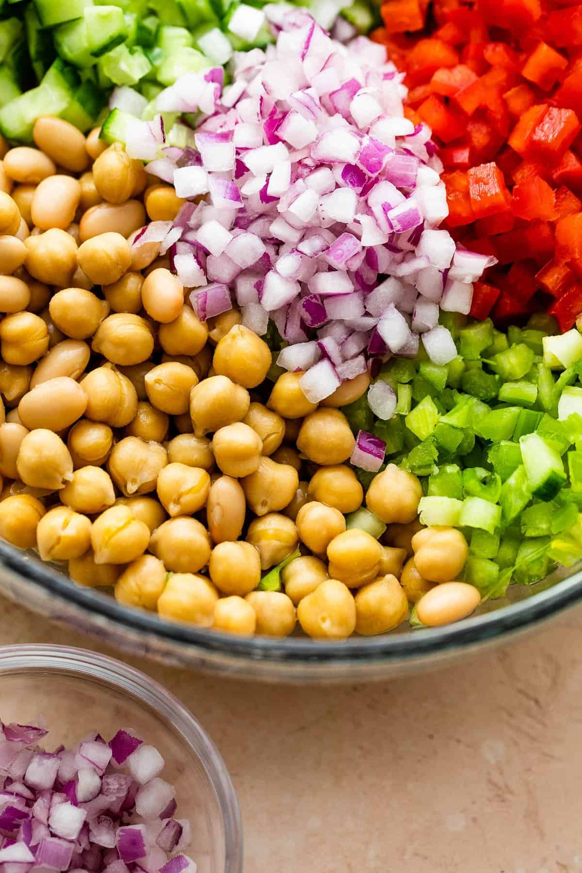 chickpeas, cucumbers, onions, and veggies arranged in a glass salad bowl