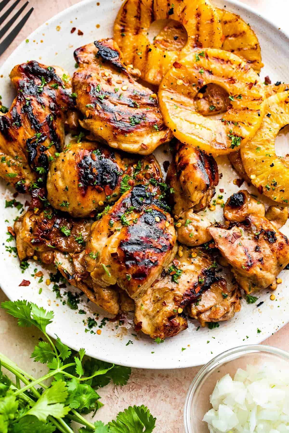 grilled chicken thighs and pineapples served on a white round plate