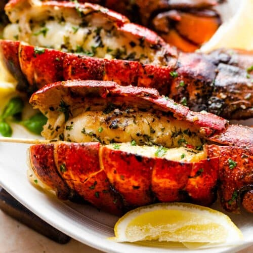 side shot of four grilled lobsters on a plate with lemon wedges
