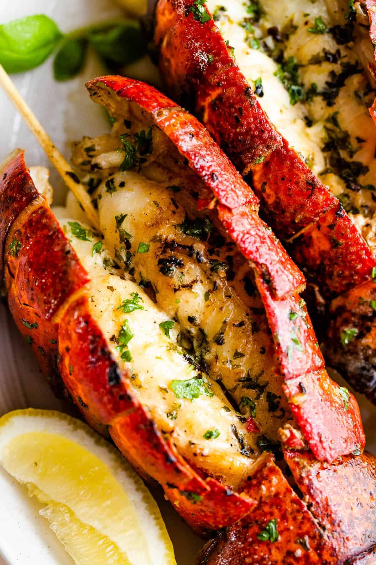 grilled lobster tail topped with parsley and served with lemon wedges