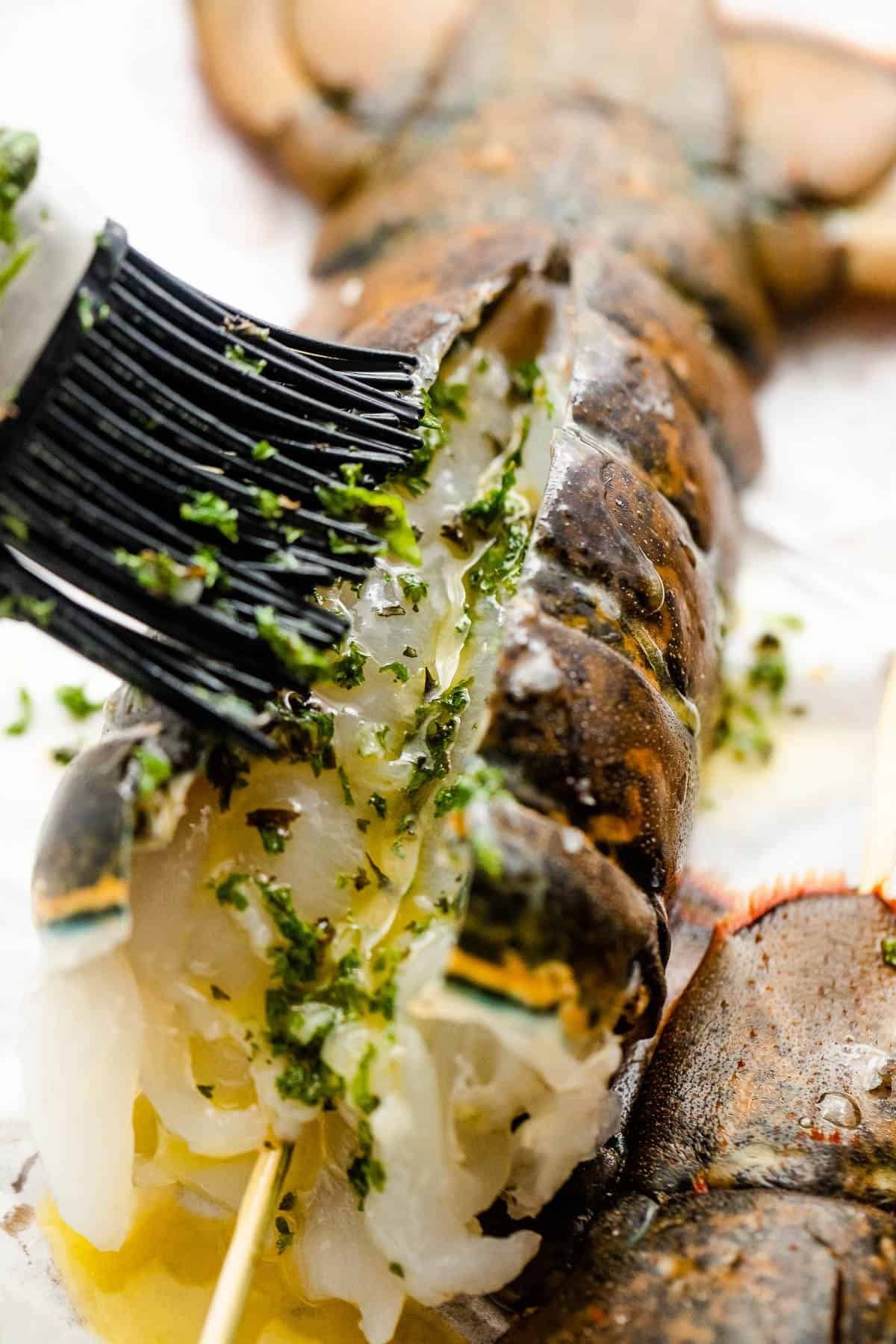 brushing raw fresh lobster with butter sauce