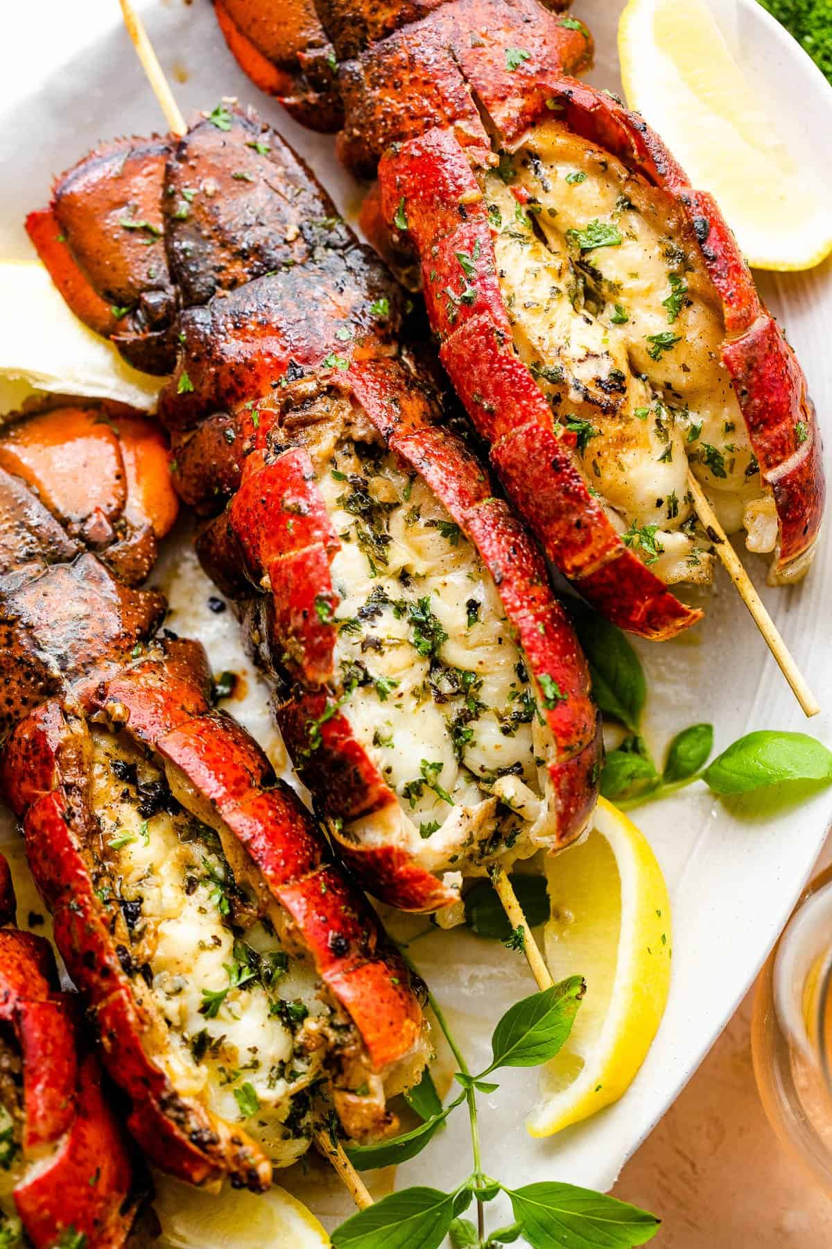 overhead shot of three grilled lobster tails served on a plate with lemon wedges and basil leaves