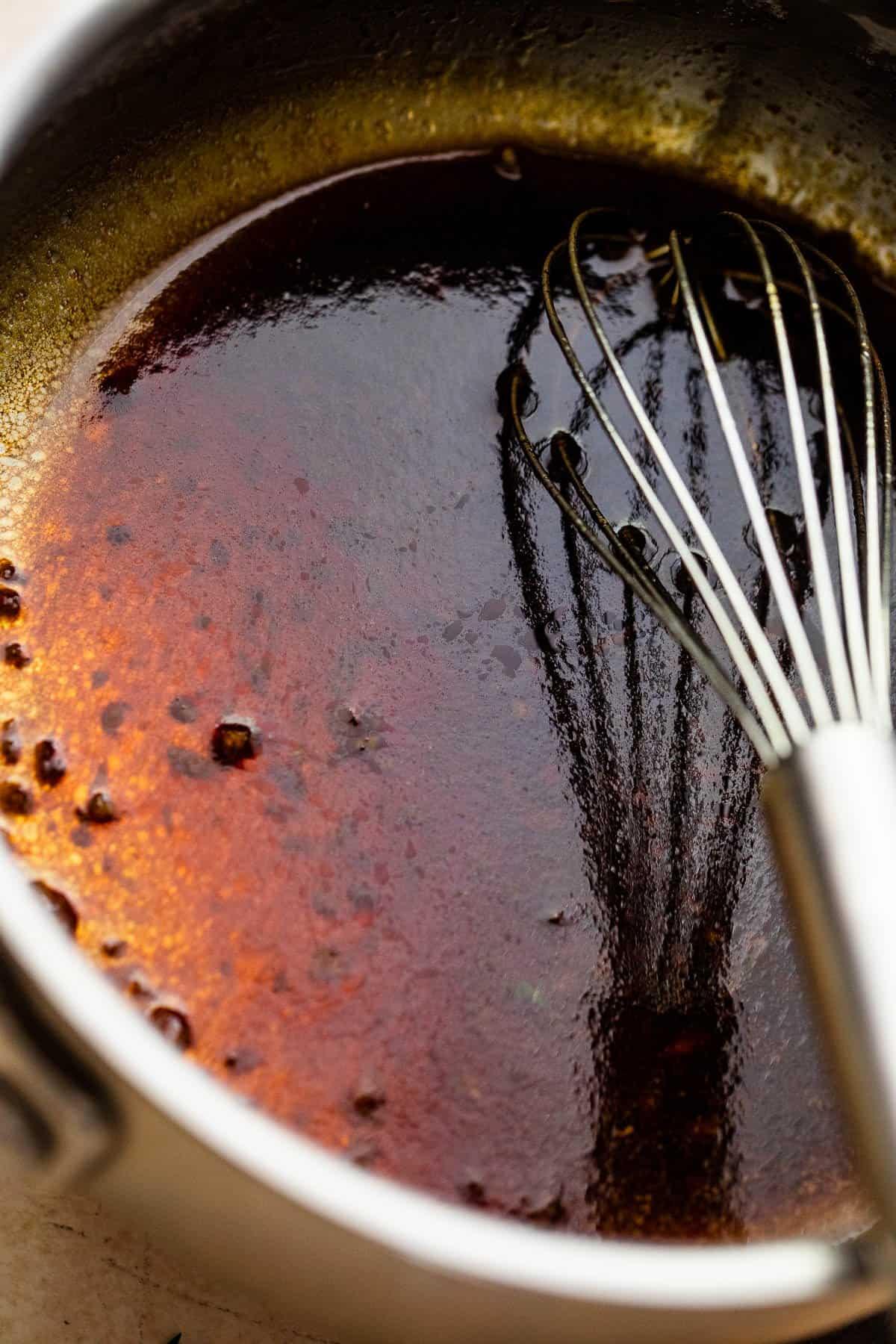 whisking sauce in a saucepan