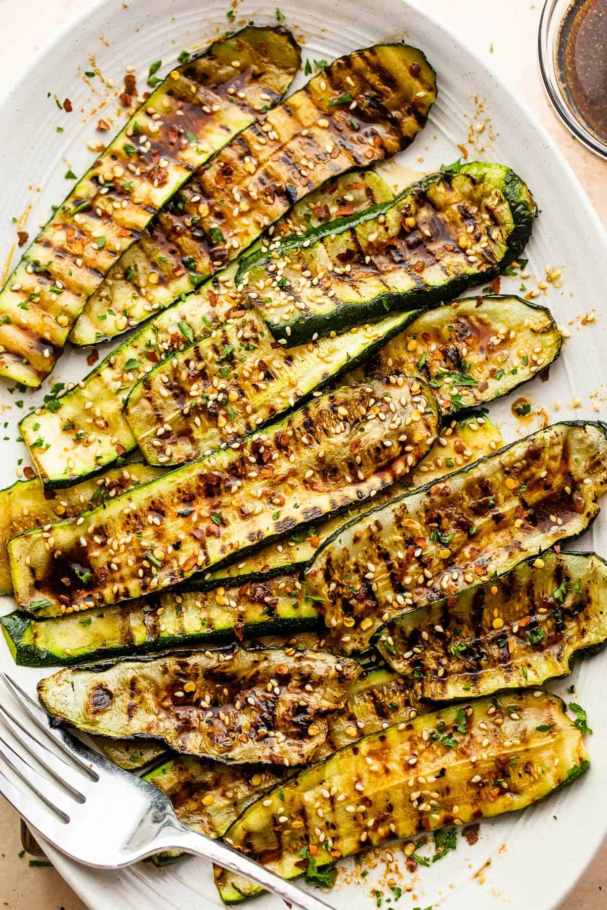 grilled zucchini slices served on a plate with a fork on the side