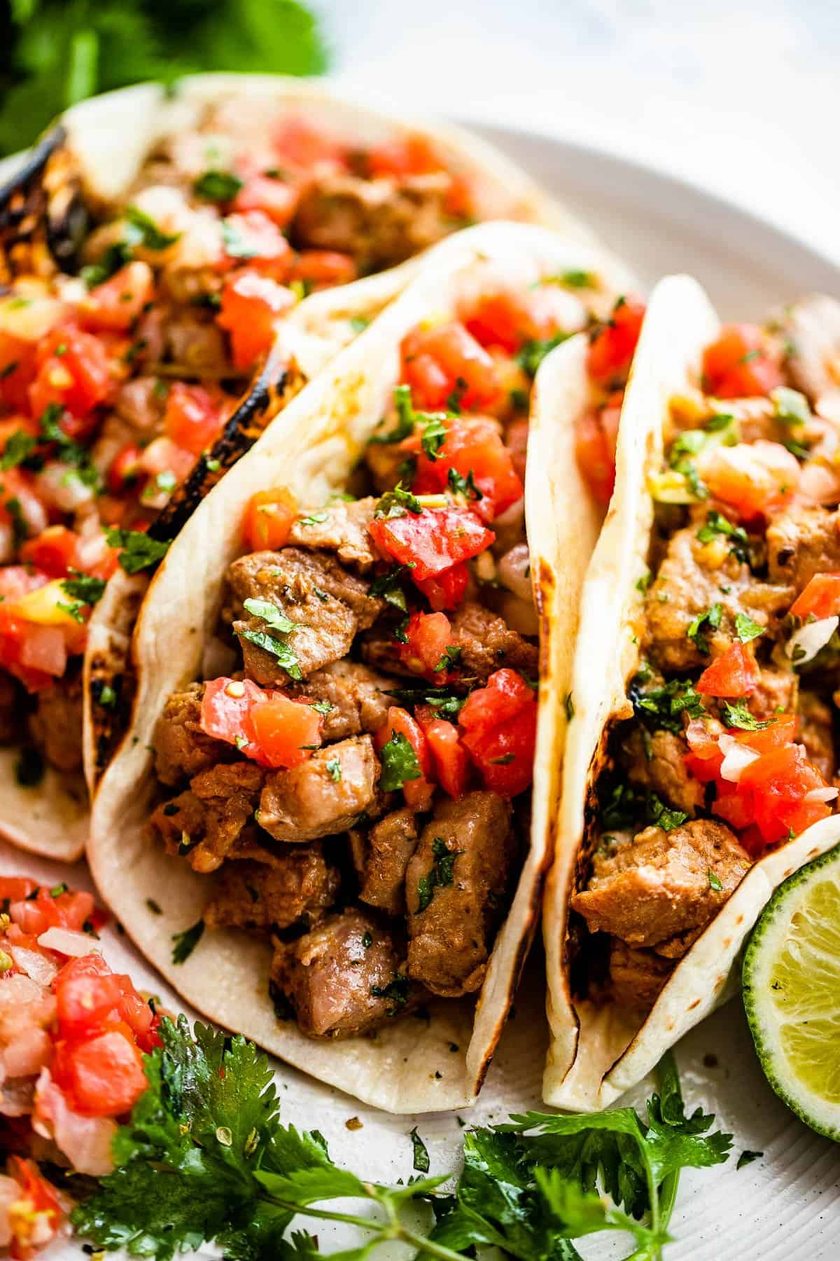 side shot of three pork carnitas tacos topped with tomatoes, cilantro, and onions
