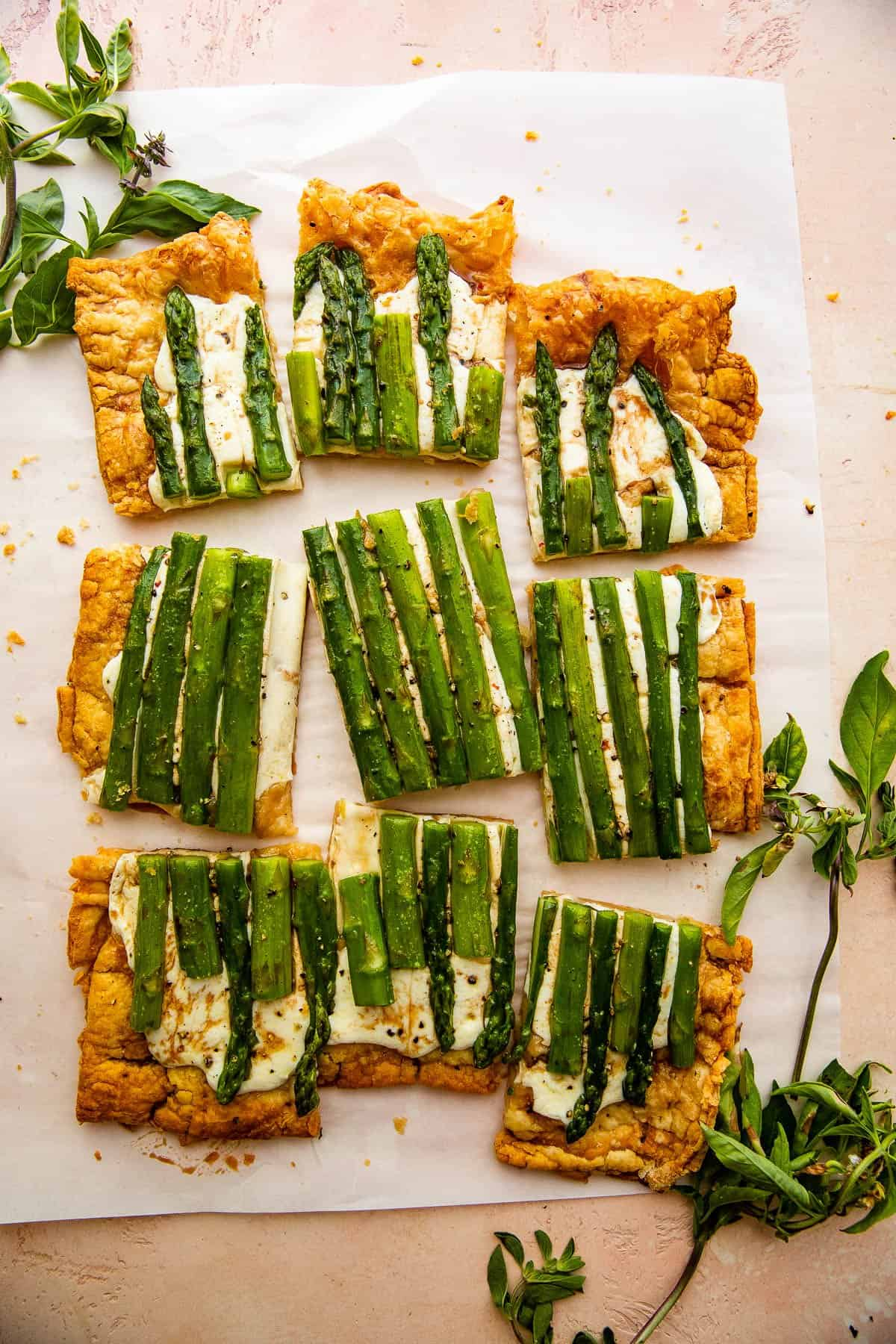 cheesy asparagus puff pastry tart cut up into nine pieces