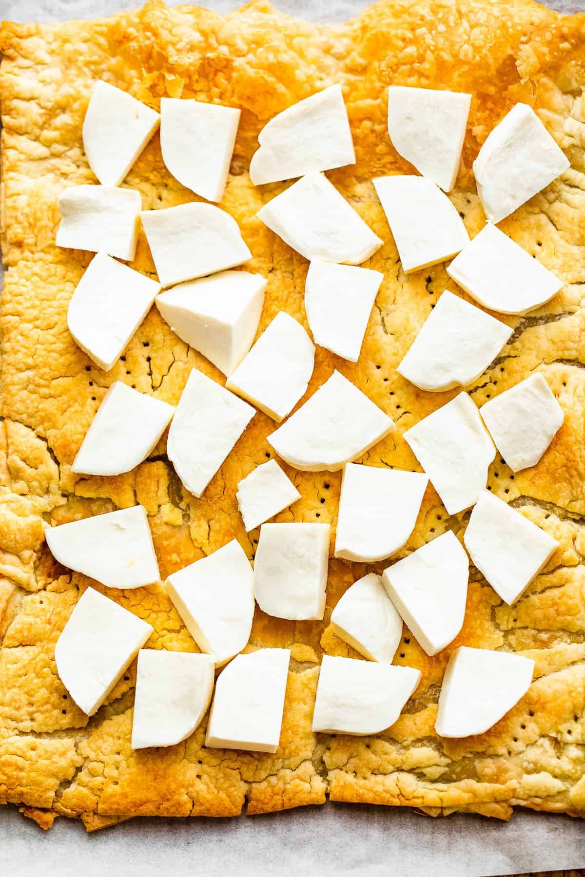 puff pastry topped with fresh chunks of mozzarella cheese