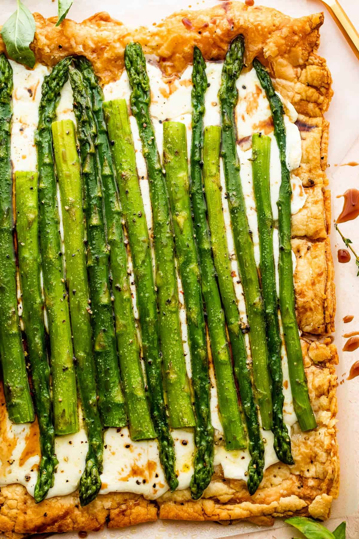 cheesy asparagus puff pastry tart drizzled with balsamic glaze