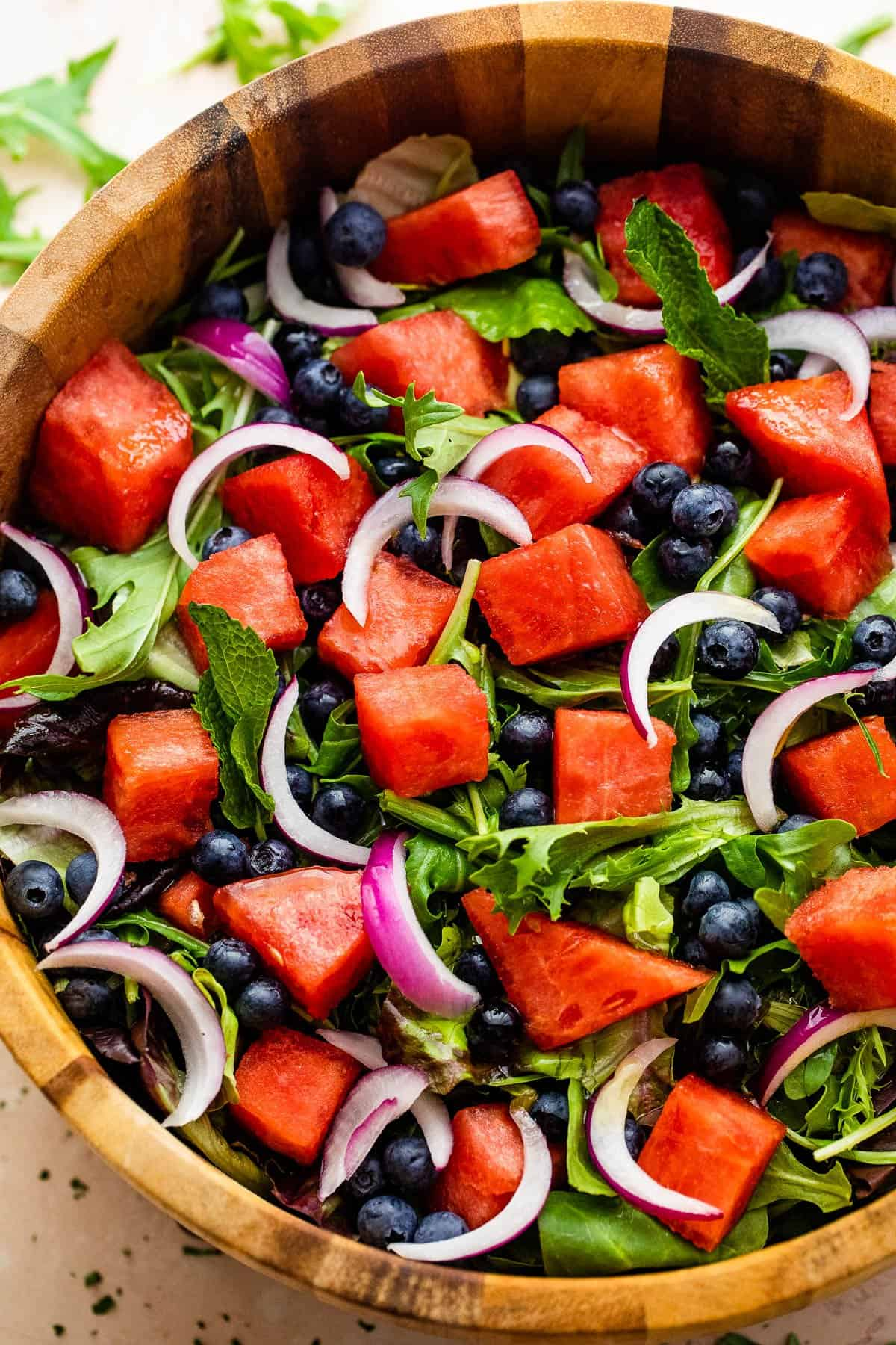cubed watermelon, blueberries, and sliced red onions atop a bed of torn up lettuce greens in a salad bowl