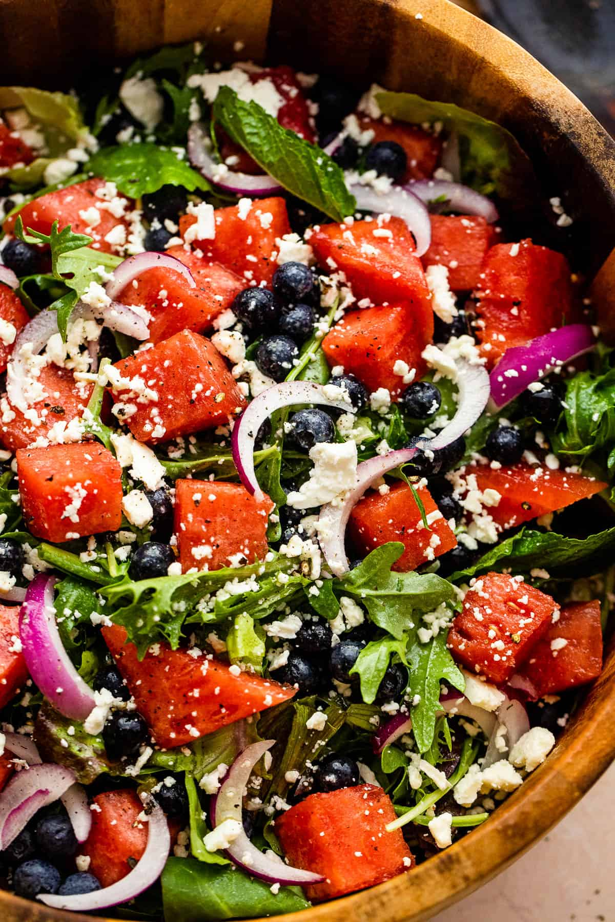 cubed watermelon, blueberries, and sliced red onions atop a bed of torn up lettuce greens and topped with feta cheese crumbles