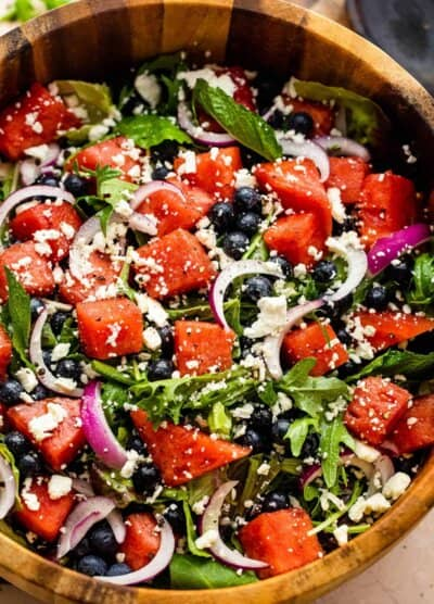 wooden salad bowl with cubed watermelon, blueberries, and sliced red onions atop a bed of torn up lettuce greens and topped with feta cheese crumbles