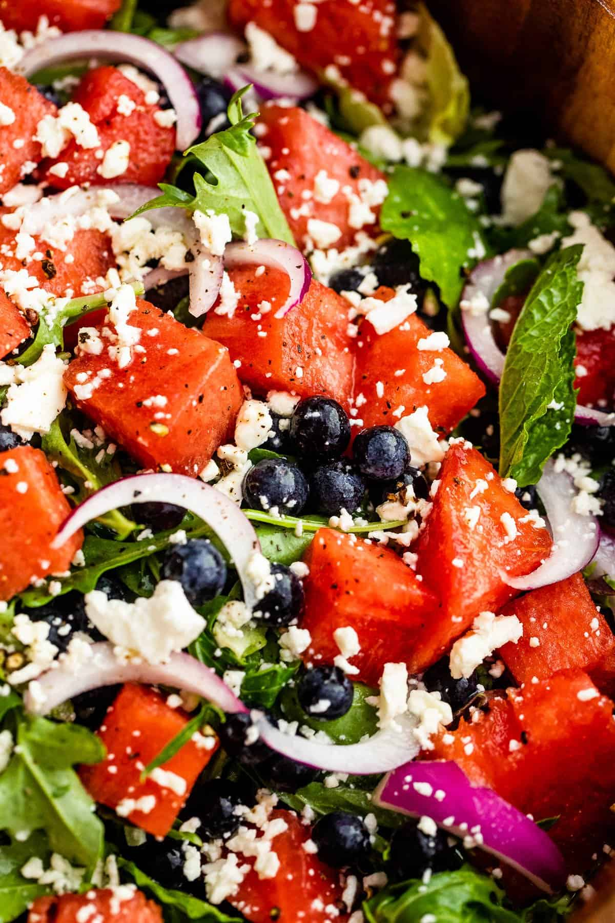 up close photo of cubed watermelon, blueberries, and sliced red onions atop a bed of torn up lettuce greens and topped with feta cheese crumbles