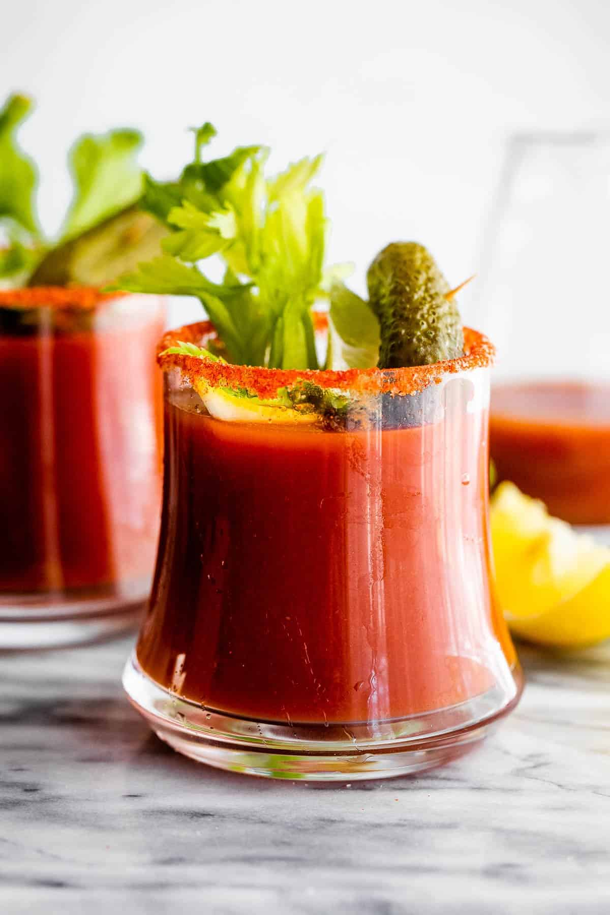 two glasses with Bloody Mary cocktail garnished with pickles and celery sticks