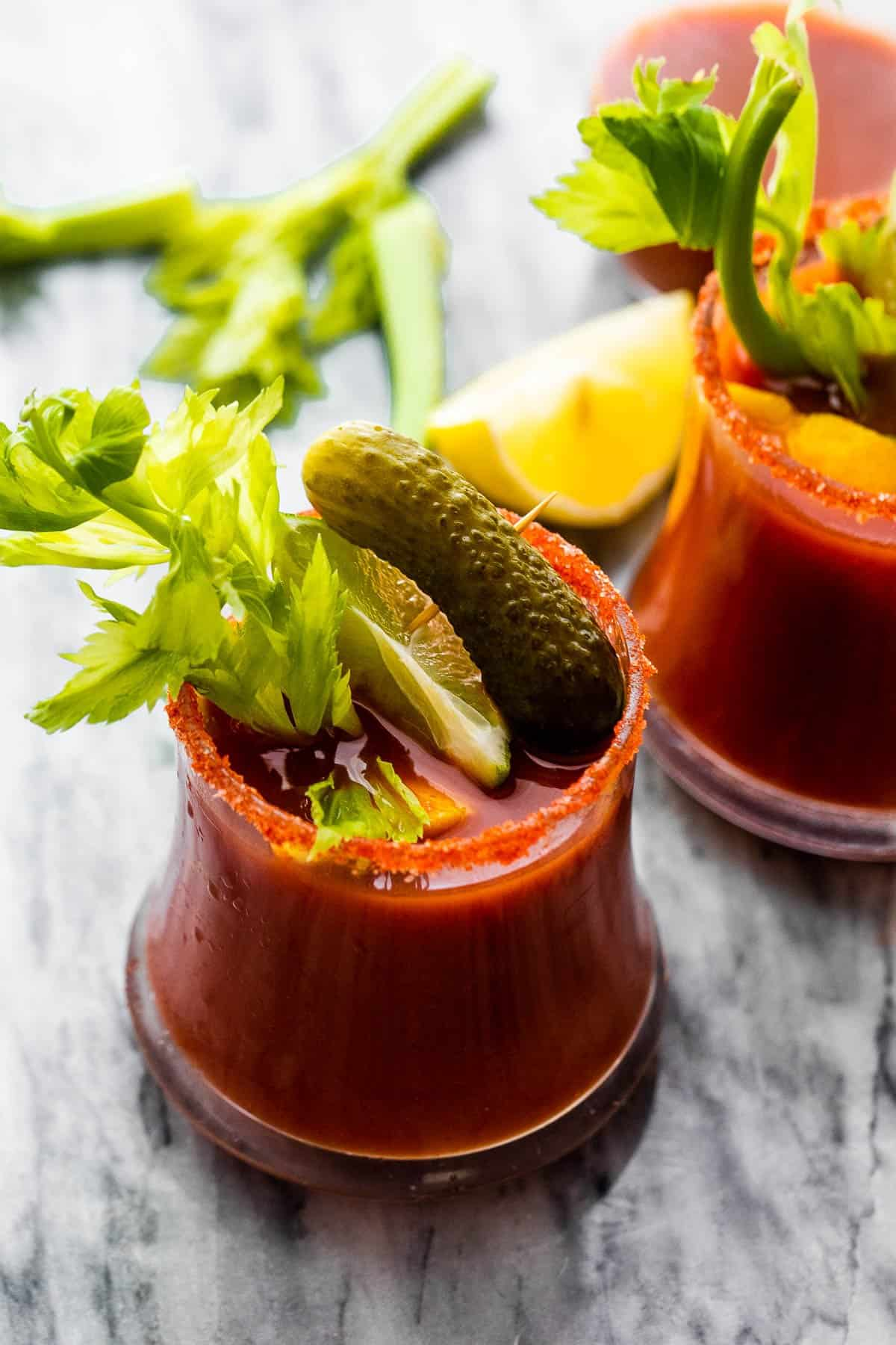 Bloody Mary cocktail garnished with pickles and celery sticks