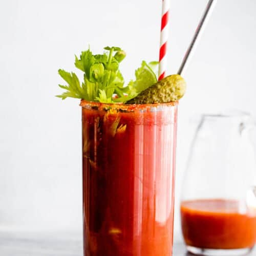 Bloody Mary cocktail garnished with straws, pickles and celery sticks