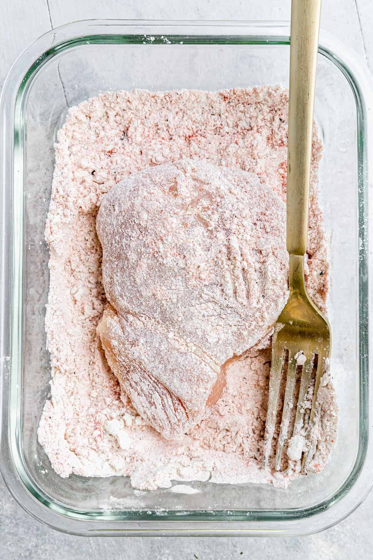 A Chicken Breast Coated in the Flour Mixture Beside a Gold Fork