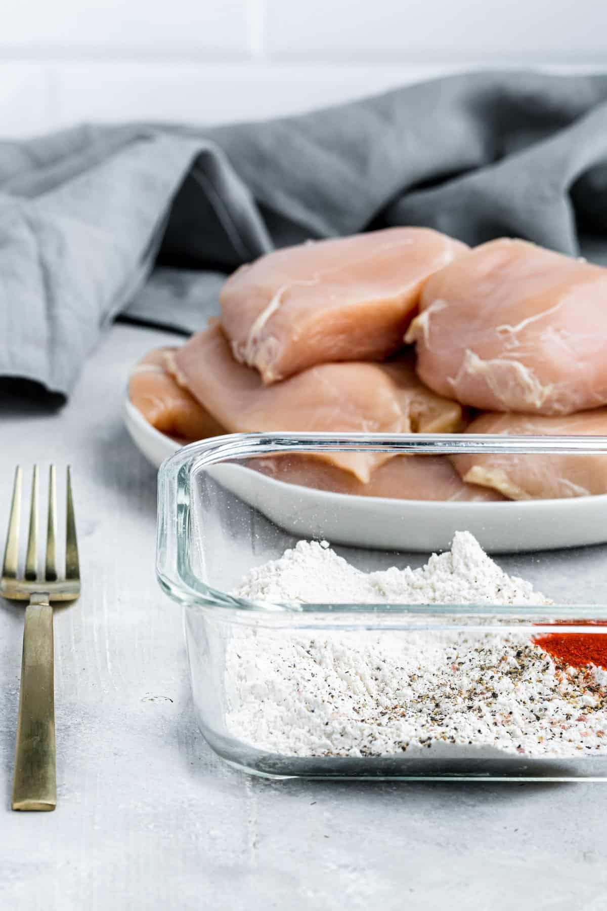 A Plate Full of Raw Chicken Breasts Beside a Baking Dish Filled with Flour, Paprika, Salt and Pepper