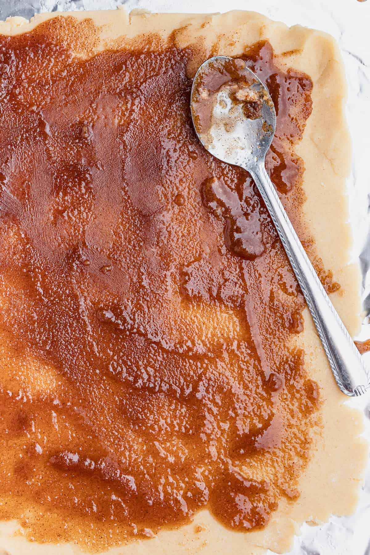 Flattened Sugar Cookie Dough with the Cinnamon Roll Filling Spread Over it Evenly
