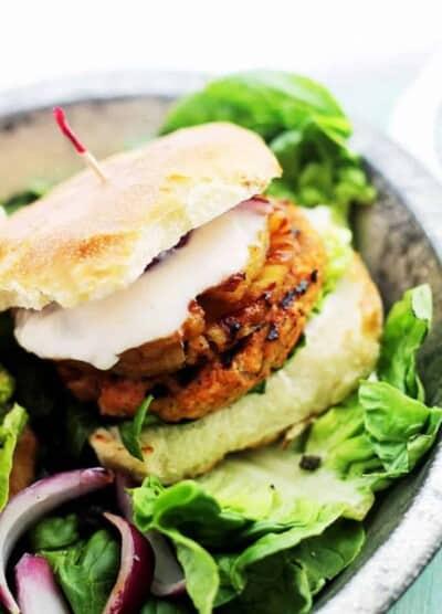 Salmon burger with sriracha yogurt sauce and a toasted bun.