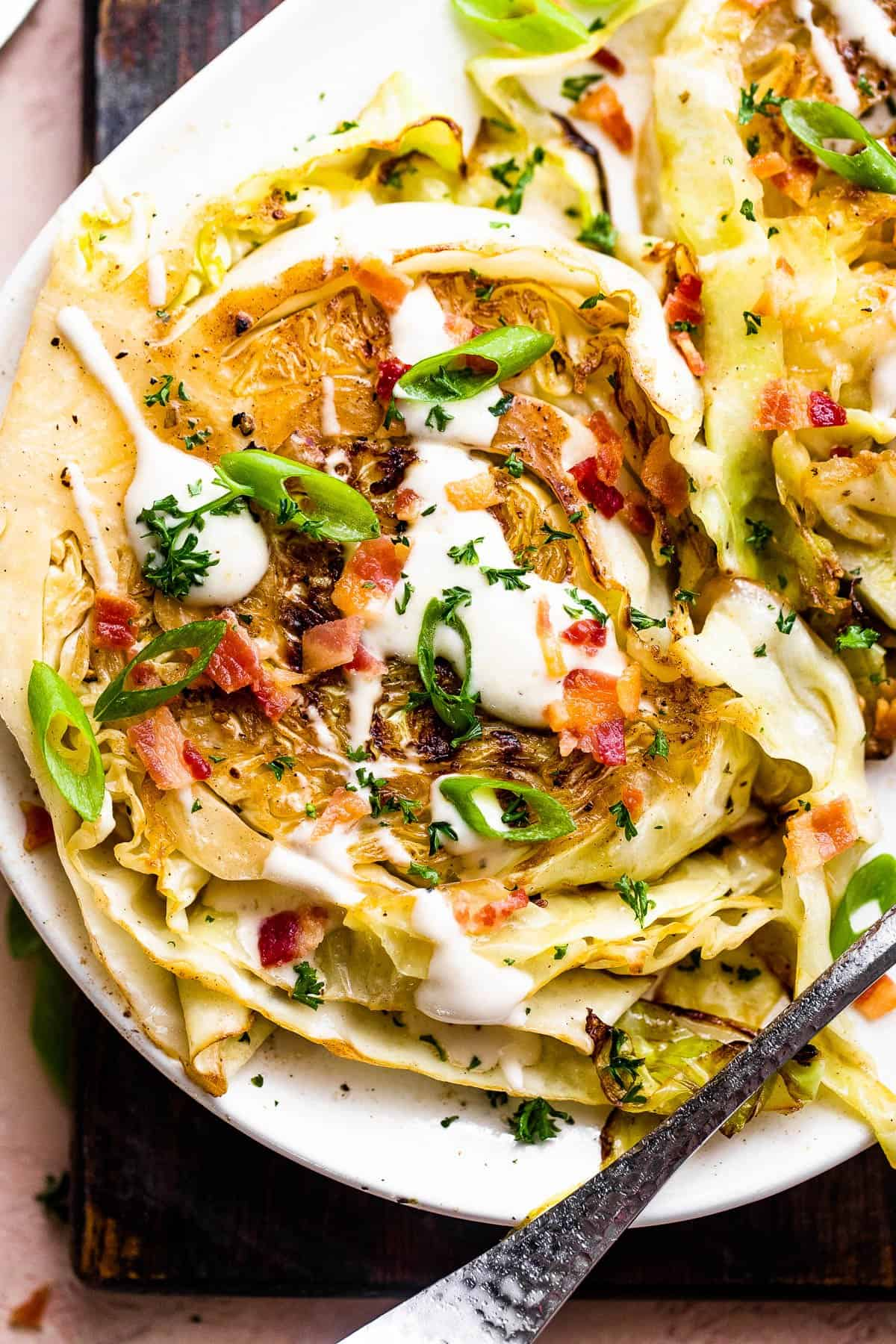 two grilled cabbage steaks topped with ranch and bacon