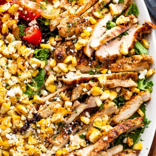 slices of chicken thighs on a bed of lettuce with halved cherry tomatoes, corn kernels, and cotija cheese