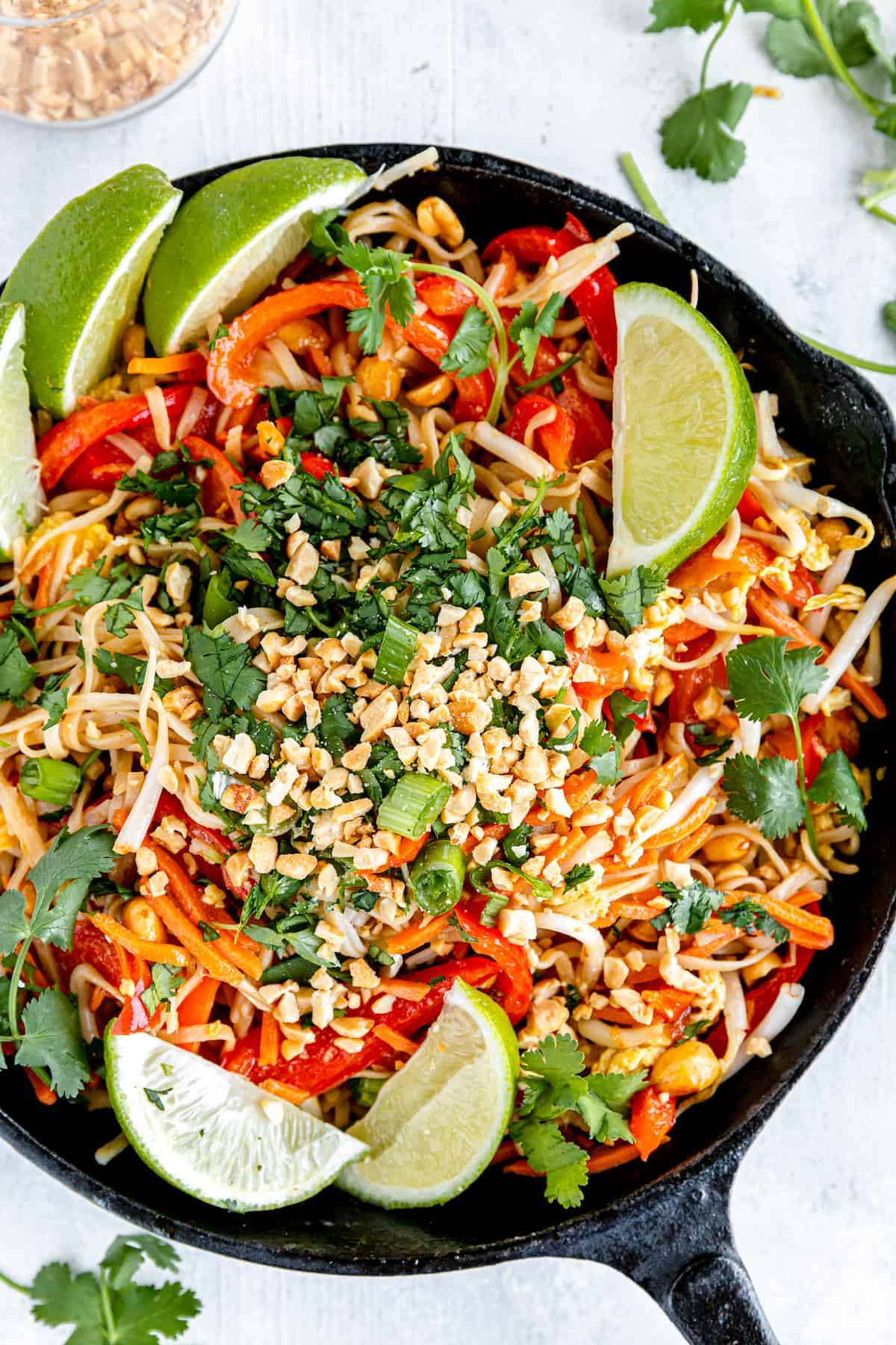 Pad Thai in a black cast iron skillet garnished with lemon wedges